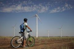 Ein junger Mann auf einem Fahrrad reitet hinter eine Windkraftanlage Stockbilder