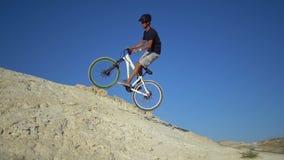 Ein junger Mann auf Fahrten eines Fahrrades von einem Berg und von den Sprüngen auf einem kleinen Hügel Langsame Bewegung stock footage