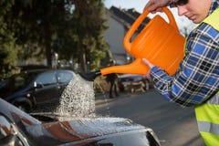 Ein junger Mann benutzt eine Gießkanne, um sein Auto zu säubern Lizenzfreie Stockfotografie