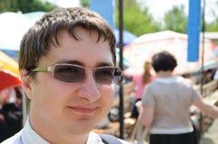 Ein junger Mann in den Gläsern von der Sonne lächelt Stockbild