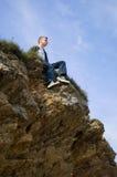 Ein junger Mann, der alleine auf der Klippe sitzt Lizenzfreies Stockbild