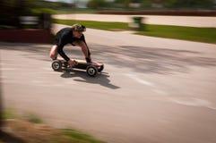 Auf ein elektrisches Skateboard schnell fahren Stockbilder