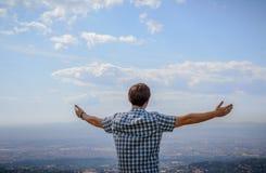 Ein junger Mann, der die Landschaft vom Hügel mit seinem Arm übersieht Lizenzfreies Stockbild