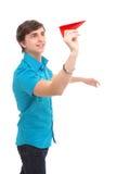 Ein junger Mann, der ein Papierflugzeug anhält Stockfotos
