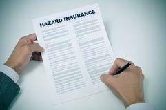 Ein junger Mann, der eine Gefahrenversicherungspolice unterzeichnet Stockbild