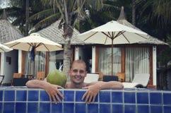 Ein junger Mann, der in einem Swimmingpool lächelt lizenzfreies stockfoto