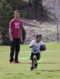 Ein junger Mann, der einen Flaggen-Fußball-Spieler trainiert Lizenzfreie Stockfotografie
