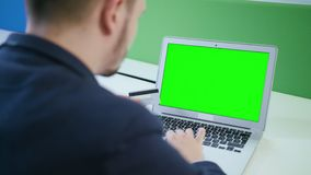 Ein junger Mann, der einen Laptop mit einem grünen Schirm verwendet stock footage