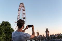 Ein junger Mann, der ein Foto des Big Ben während der Erneuerung macht stockbilder