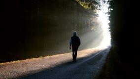 Ein junger Mann, der hinunter die Straße im Morgensonnenaufgang geht stock footage