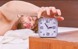 Ein junger Mann, der im Bett aufwacht und seine Arme ausdehnt Bemannen Sie glaubenden hinteren Schmerz im Bett, nachdem Sie gesch lizenzfreies stockbild