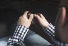 Ein junger Mann, der joypad hält und Videospiele, entspannendes hav spielt stockbilder