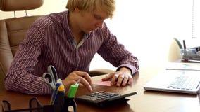 Ein junger Mann, der mit einem Taschenrechner arbeitet und etwas in einem Büro notiert stock video footage