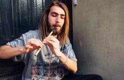 Ein junger Mann, der mit Flöteninstrument auf der Straße, Ausführender des jungen Mannes durchführt lizenzfreie stockfotografie