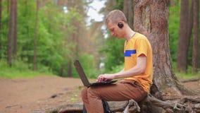 Ein junger Mann, der Musik auf Kopfhörern hört und ein Buch liest stock video footage