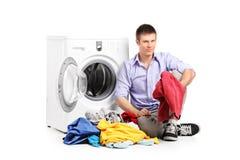 Ein junger Mann, der nahe bei einer Waschmaschine sitzt Stockfoto