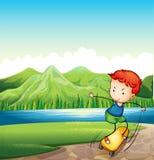 Ein junger Mann, der am Riverbank Skateboard fährt Stockfotografie