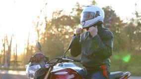 Ein junger Mann in der schwarzen Lederjacke sitzt auf Motorrad, verschiebt Sonnenbrillen und setzt an weißen Sturzhelm vor Reise  stock video footage