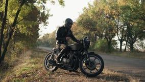 Ein junger Mann in der schwarzen Lederjacke sitzt auf seinem Motorrad und setzt einen schwarzen Sturzhelm, um auf eine Reise im W stock video
