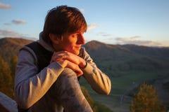 Ein junger Mann, an der Spitze des Berges, passt die Sonne auf, unterzugehen Stockbilder