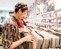 Ein junger Mann, der Vinylaufzeichnungen in einem Speicher oder in einem Geschäft betrachtet stockbild