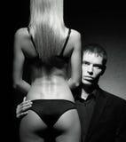 Ein junger Mann, der von der Rückseite einer sexy Frau schaut Stockfotos