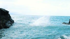 Ein junger Mann, der von einer Klippe in das blaue Meer springt Aktive und Spa?sommerferien