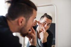 Ein junger Mann, der zuhause im Spiegel, einen Pickel zusammendrückend schaut lizenzfreie stockfotografie