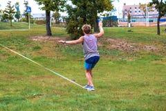 Ein junger Mann in einem allgemeinen Park lernend, ein Drahtseil zu gehen stockbild