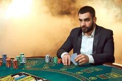 Ein junger Mann in einem Anzug, der am Pokertisch sitzt Mannglücksspiele Der Spieler an den Spielkarten des Spieltischs lizenzfreie stockfotos