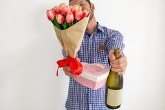 Ein junger Mann in einem blauen karierten Hemd dehnt einen Blumenstrauß von Tulpen, von Herz-förmigen Geschenkbox und von Flasche lizenzfreie stockbilder