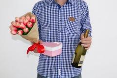 Ein junger Mann in einem blauen karierten Hemd und in Jeans, einen Blumenstrauß von Tulpen, eine Herz-förmige Geschenkbox und ein stockfoto