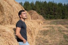 Ein junger Mann in einem grauen T-Shirt und in den Jeans steht an einem Heuschober, Atmungsreine luft, Frische, stillstehen nach  stockfotos