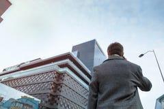Ein junger Mann in einem Mantel macht einen anonymen Telefonanruf, der nahe dem Geschäftszentrum steht lizenzfreies stockfoto