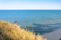 Ein junger Mann in einem roten Hemd sitzt auf einem Hügel im Hintergrund des Meeres stockfotos
