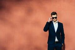 Ein junger Mann in einem schwarzen Anzug auf einem Hintergrund einer Backsteinmauer Stockfotografie