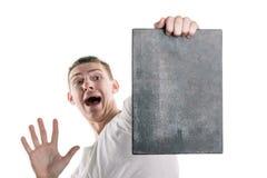 Ein junger Mann in einem T-Shirt mit einer Fahne für Ihren Text oder noch etwas, Blicke auf die Fahne mit Furcht Horizontaler Rah Stockbilder