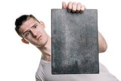 Ein junger Mann in einem T-Shirt mit einer Fahne für Ihren Text oder noch etwas, Blicke auf die Fahne mit horizontalem Rahmen des Lizenzfreie Stockbilder