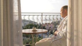 Ein junger Mann in einem trinkenden Kaffee der weißen Robe auf der Terrasse 4K stock video