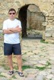 Ein junger Mann in einem weißen T-Shirt und in der Sonnenbrille steht auf der Wand der Festung stockbild