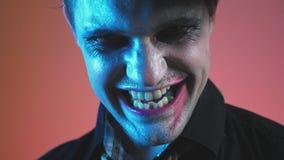 Ein junger Mann in einem Zombiehalloween-Kostüm, Blick auf die Kamera und Lächeln ominös 4k, Zeitlupe stock video footage