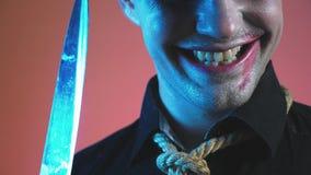 Ein junger Mann in einem Zombiehalloween-Kostüm, Blick auf die Kamera und Lächeln ominös 4k, Zeitlupe stock footage