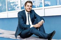 Ein junger Mann in einer blauen Klage, die auf einer Wand sitzt Lizenzfreie Stockfotografie