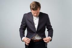 Ein junger Mann in einer stilvollen Jacke kennt nicht in den Regeln der Etikette aus Er denkt an, ob man Knopf befestigt stockfotografie