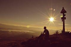Ein junger Mann fühlt sich in den Bergen bei Sonnenaufgang frei Lizenzfreie Stockfotos