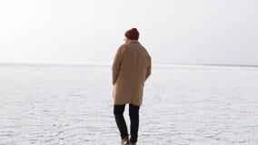 Ein junger Mann geht auf das Eis im Winter lizenzfreies stockfoto