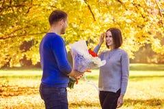 Ein junger Mann gibt seiner Frau einen Blumenstrauß lizenzfreie stockfotos