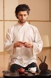 Ein junger Mann hält eine chinesische Tezeremonie an stockfoto