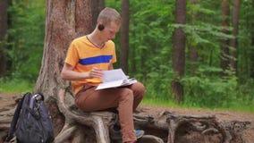 Ein junger Mann im Wald liest ein Trainingsbuch stock footage
