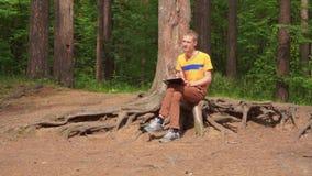 Ein junger Mann im Wald sitzt und malt ein Bild mit einem Bleistift stock footage